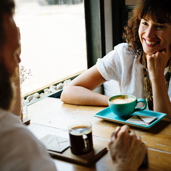 A woman and man enjoying a cup of coffee in a cafe