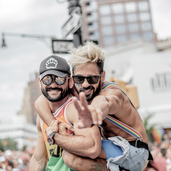 A young gay couple celebrating on the streets of a city