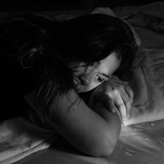 A depressed young woman lying on her bed