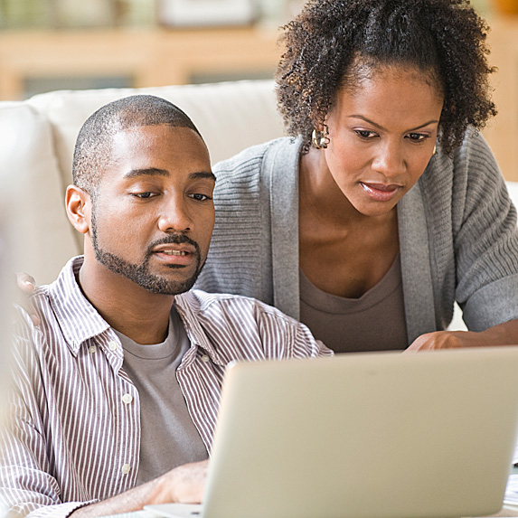 Worried man and woman looking at laptop