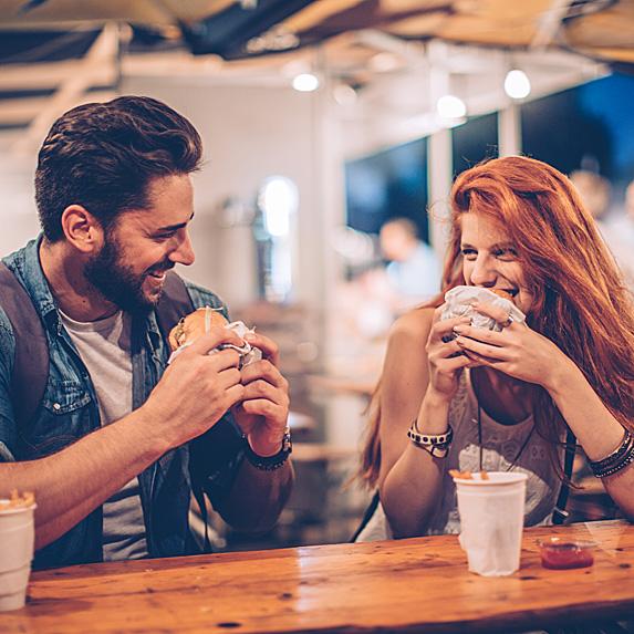 Man and woman eating burgers at a bar