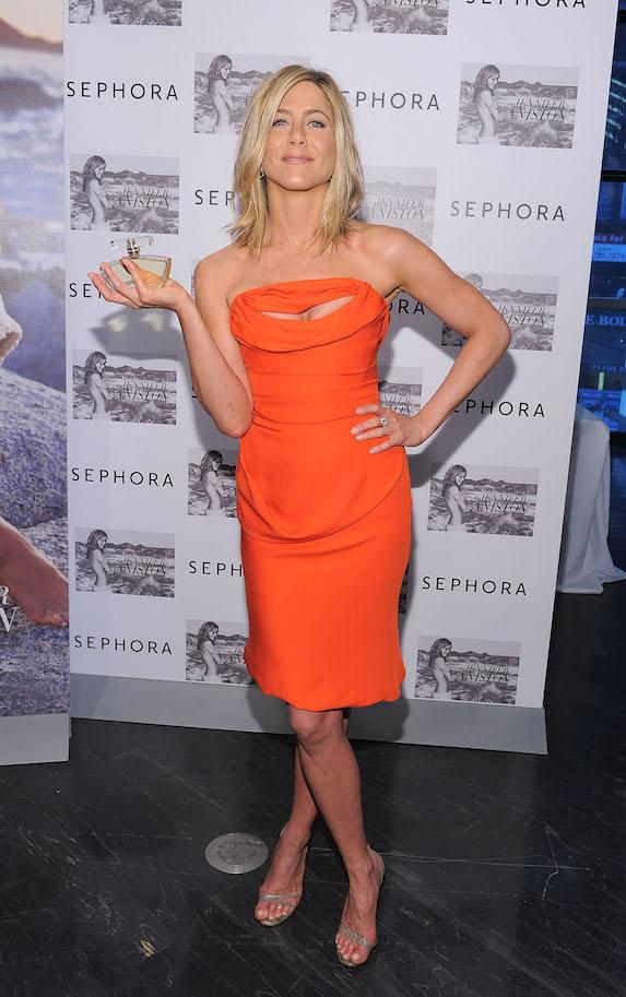 Jennifer Aniston wears an orange midi dress to debut her fragrance in 2011