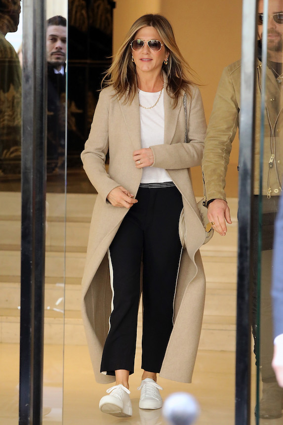 Jennifer Aniston wears black pants and a white tee shirt with a tan coat and white sneakers while in Paris, France in 2017