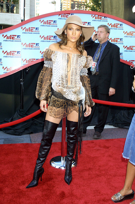 Jennifer Lopez wears a hat, sheer tunic mini dress and thigh-high boots to the 2001 MTV Awards