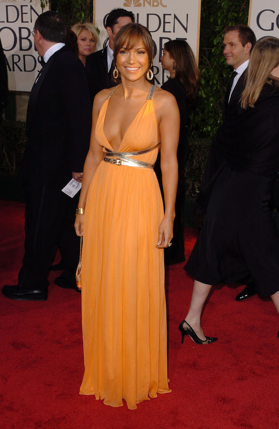 Jennifer Lopez wears a bright orange gown by Michael Kors to the Golden Globe Awards in 2004