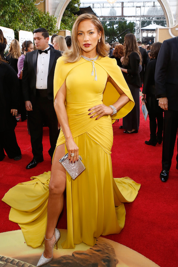 Jennifer Lopez wears a canary-yellow caped dress by Giambattista Valli to the Golden Globes in 2016
