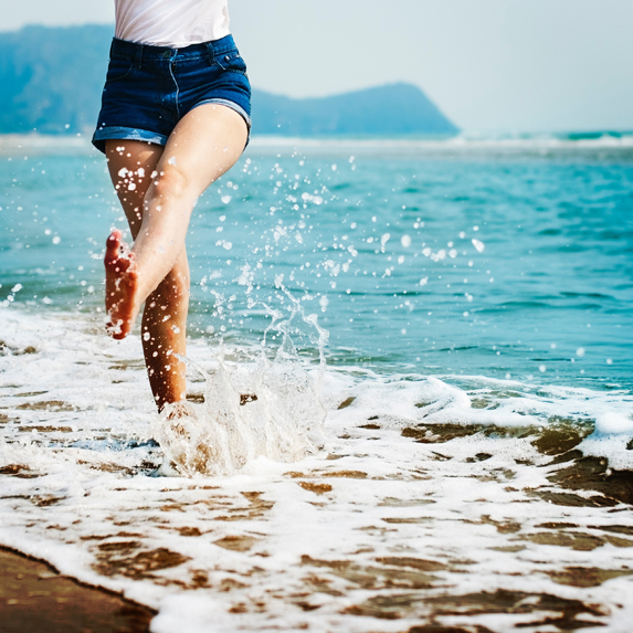 A woman's legs kicking water around in the ocean