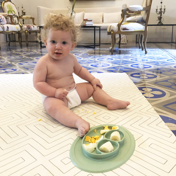 Adorable baby has a picnic on a fancy floor