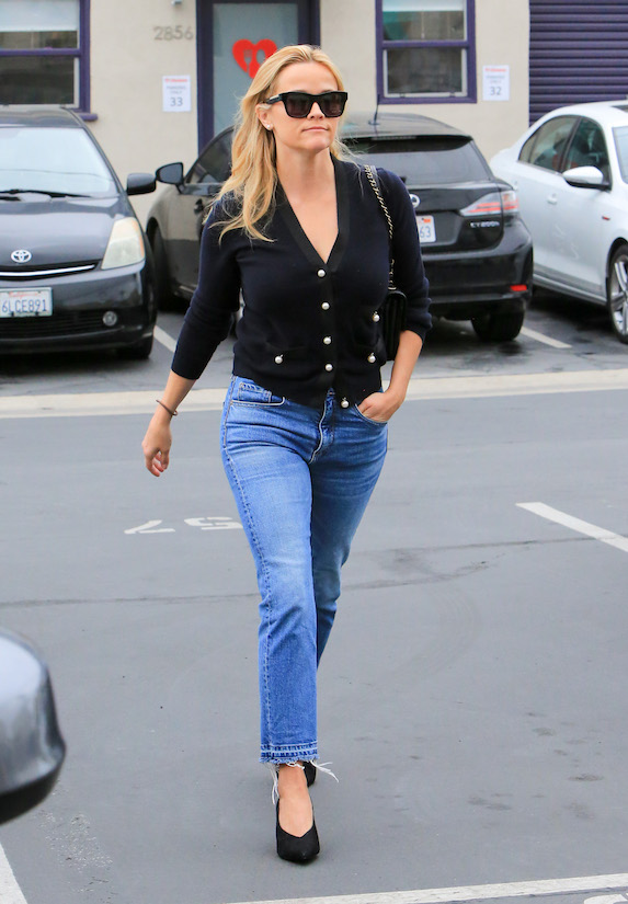 Reese Witherspoon wears jeans, black pumps and a black cardigan