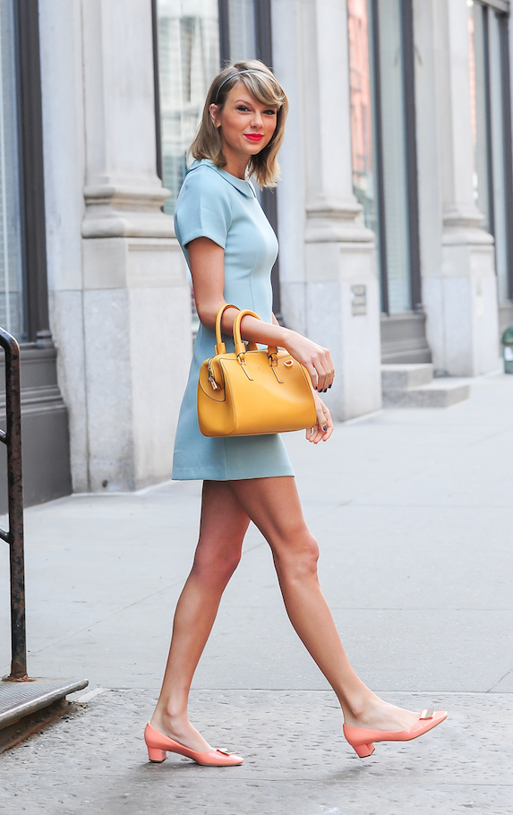 Taylor Swift wears a mini dress with kitten-heel shoes and a yellow handbag