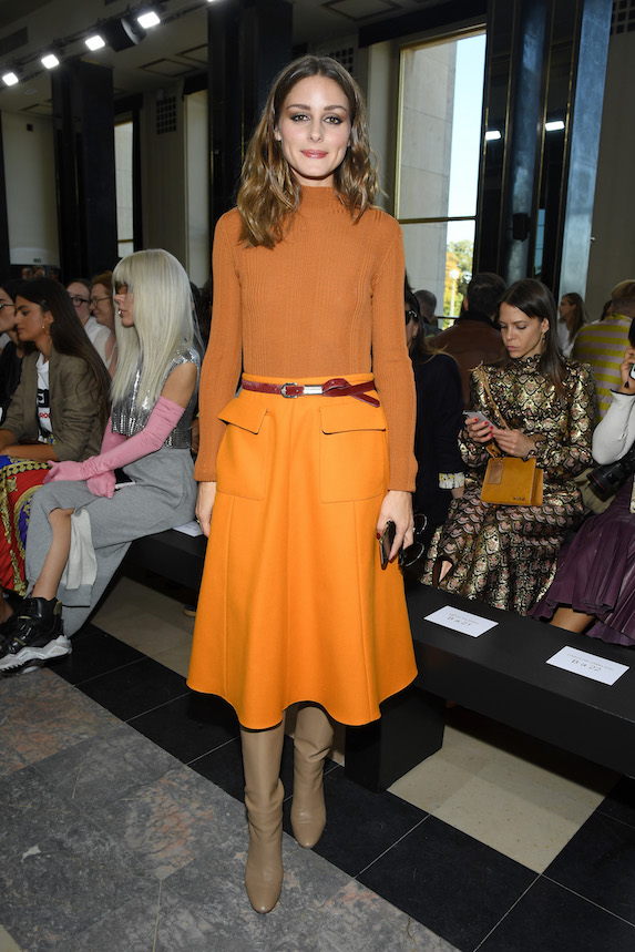 Olivia Palermo wears coordinated orange skirt and knit with beige boots