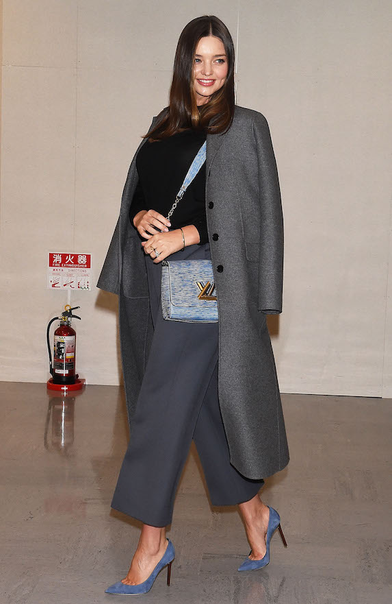 Miranda Kerr wears gray trousers and coat with a black knit top and blue-gray shoes and bag