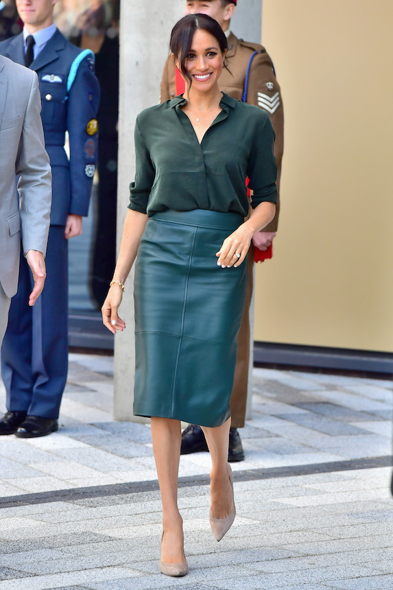 Meghan Markle wears a green blouse and coordinating leather pencil skirt
