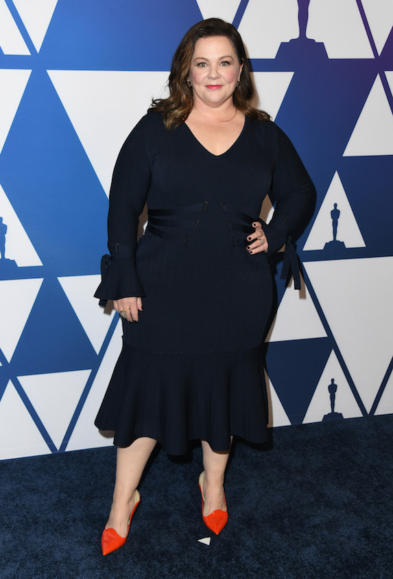 Melissa McCarthy wears a black dress and bold red statement heels