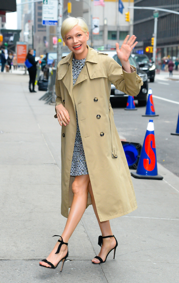 Michelle Williams wears a trench coat and dress with black high heels