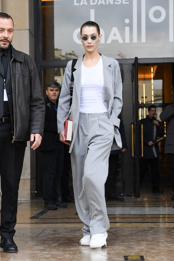 Model Bella Hadid wears an oversized gray suit with a white t-shirt underneath