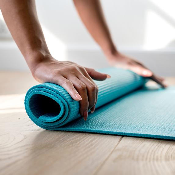A woman's hands rolling up a blue yoga mat