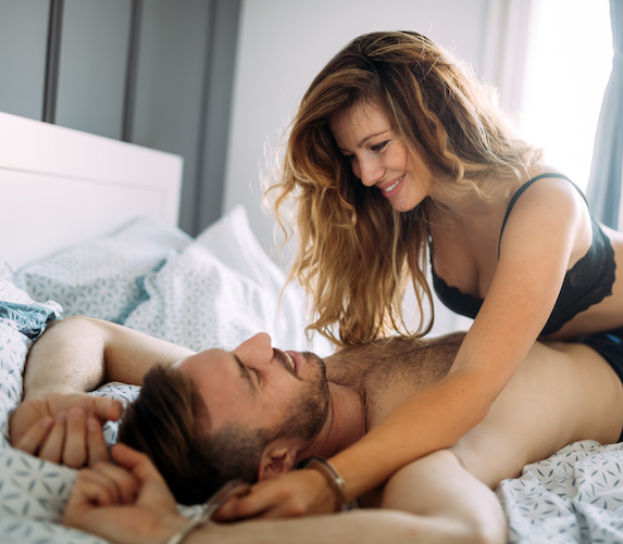 Woman in lingerie lies playfully on top of a man in bed