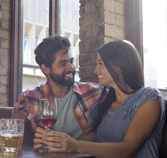 Man and woman drinking and smiling while sitting together in a restaurant booth