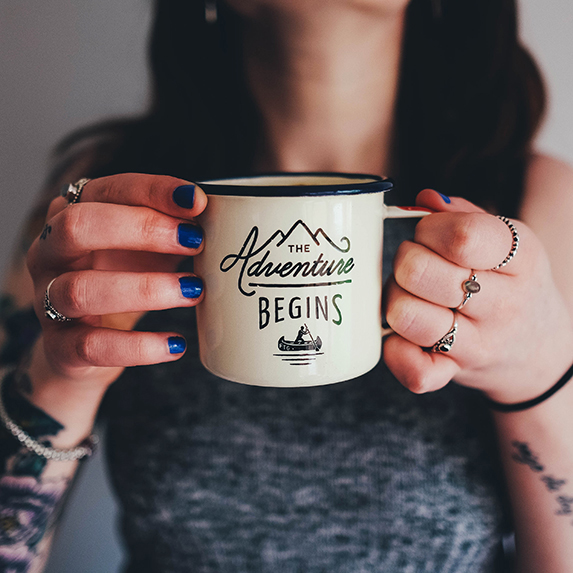 Woman holding an adventure mug