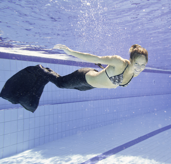 Woman wears a mermaid tail while swimming under the water in a pool