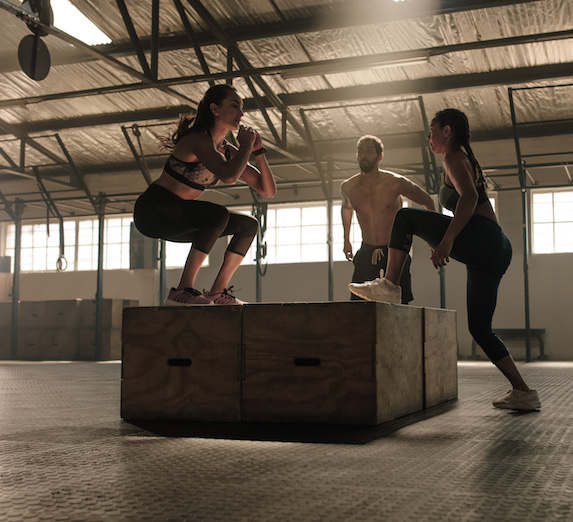 Small group doing box-jumping workout in a crossfit gym