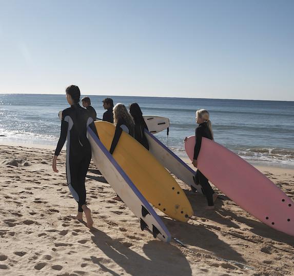 Surfers walking toward the water