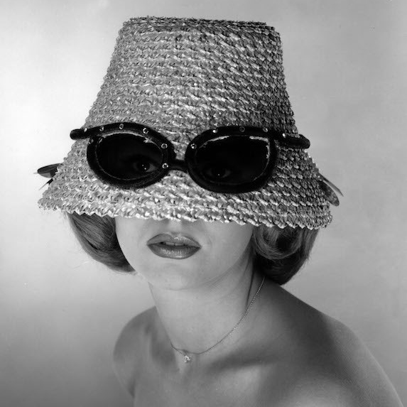 A model wears a straw hat, pulled down over her eyes with a pair of sunglasses fitted overtop of the hat