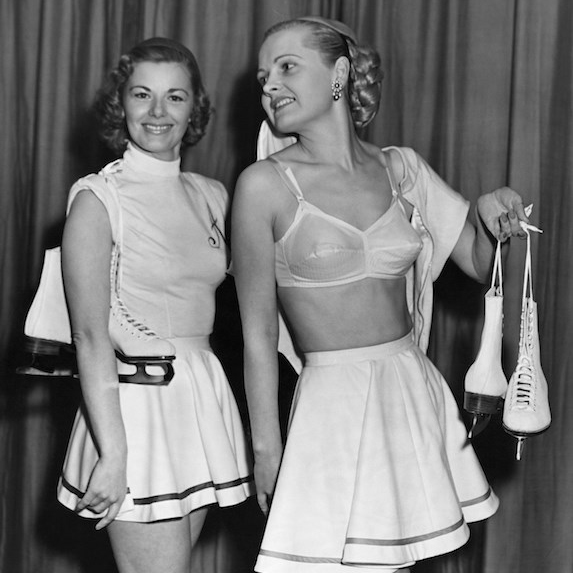 Two models from the early 1950's smile in a candid photo, where one model wears a skirt with no blouse, revealing her fashionable chansonette bra