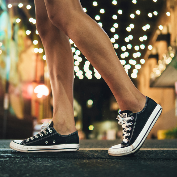 Woman walking with low top Chuck Taylors