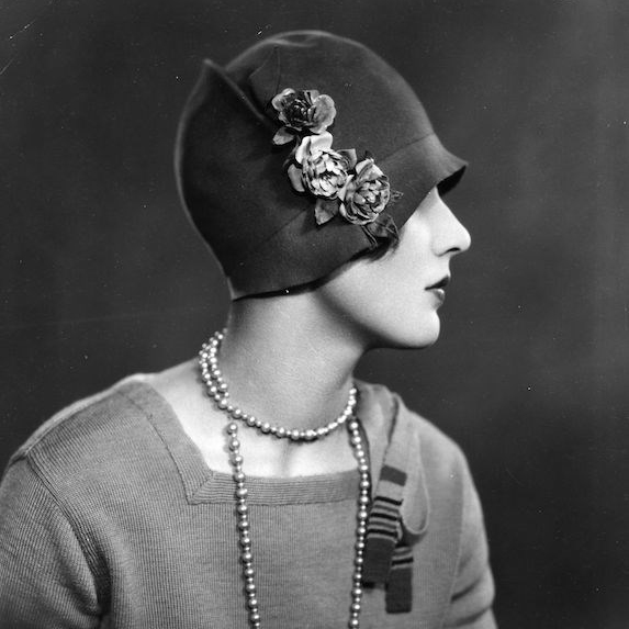 Black and white photo of a woman in side profile wearing a 1920's cloche hat