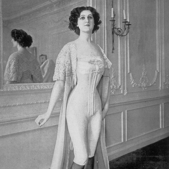 Woman in a black and white photo wearing an Edwardian-style corset and other undergarments fashionable in the early 1900's
