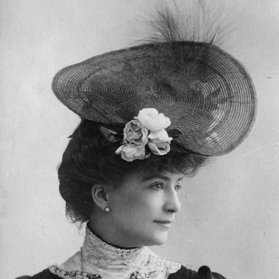 A woman poses for a black and white photo dated to the 1900's, wearing a hat adorned with feathers