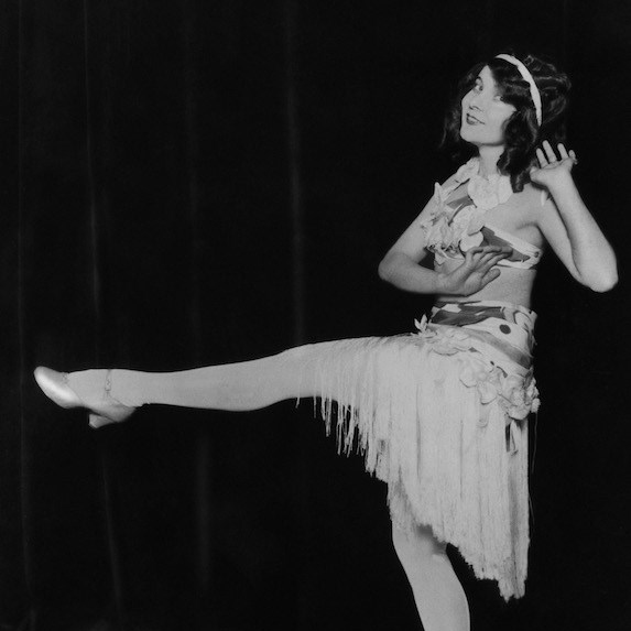 Black and white photo of a woman wearing a flapper dress, posing with one leg up in the air