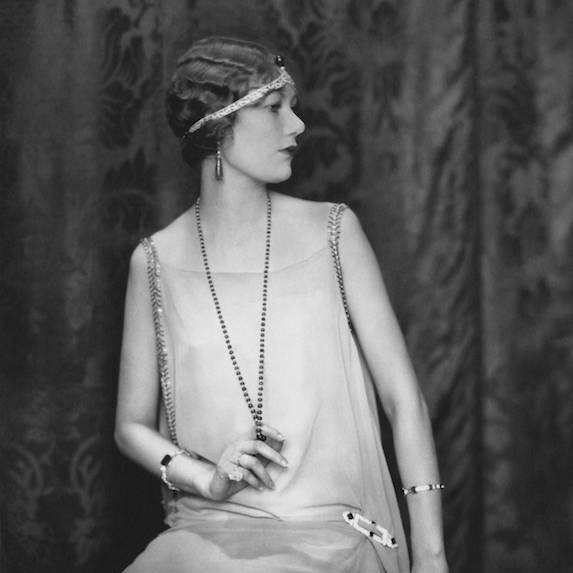 Black and white photo of a woman dressed in flapper-style clothing, with a pixie cut hairstyle and flapper headband accessory