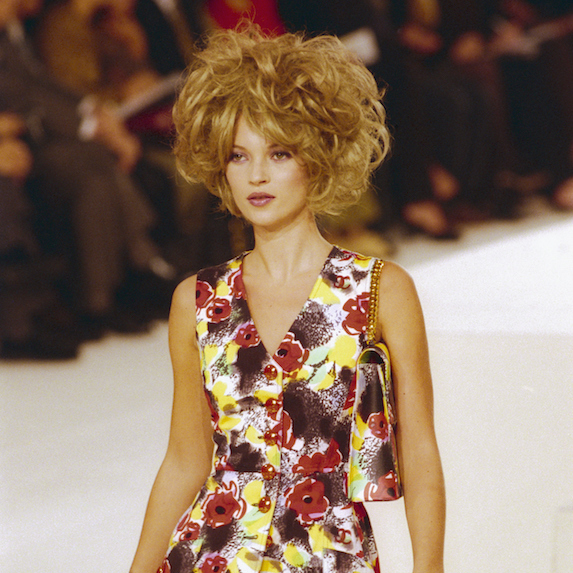 Kate Moss walks the runway in the 1990's wearing a short floral dress