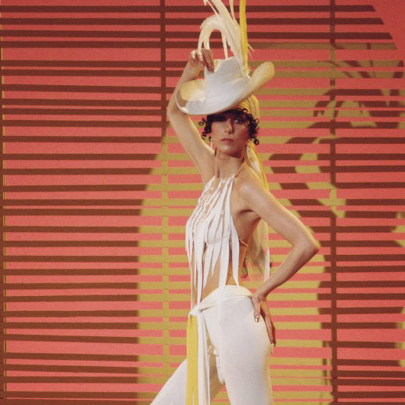Cher poses for a 1972 promotional photo wearing a white fringed outfit