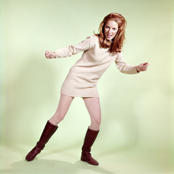 1960's model in a red jumpsuit wears white go-go boots