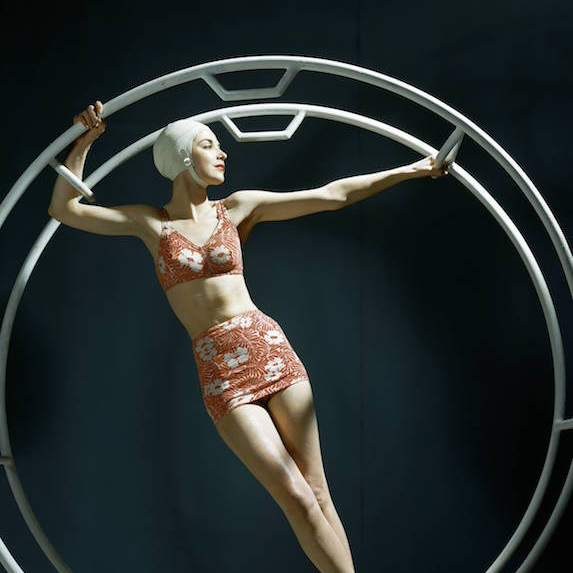 Woman in a bathing cap poses while standing in a large metal hoop, wearing a floral print bikini
