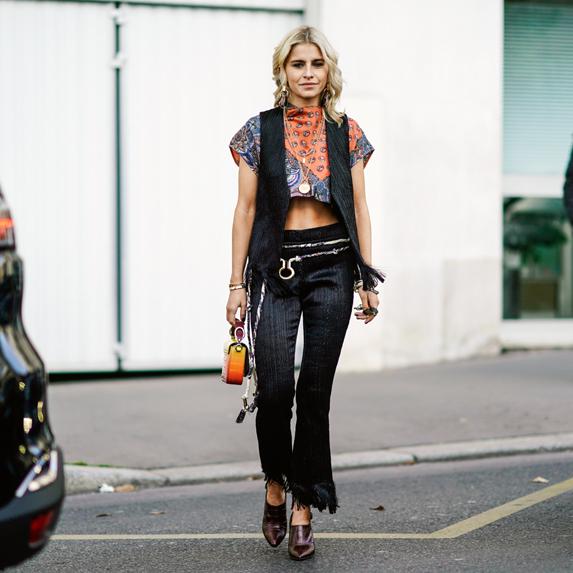 Caroline Daur wears bell bottoms, an oversized cropped jacket, cap and plaid bag with platform shoes