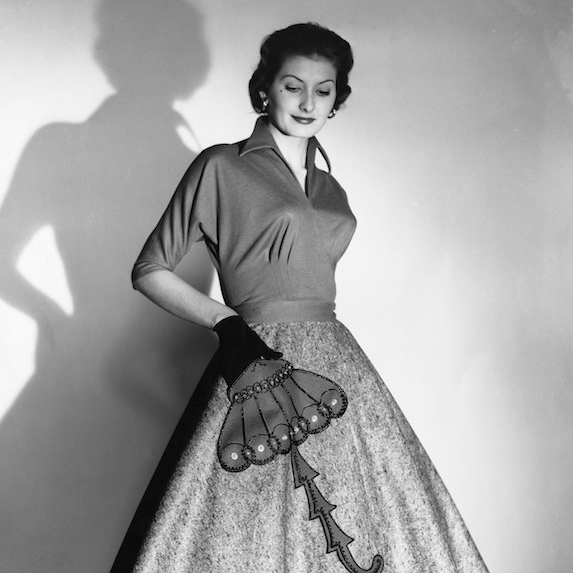 Black and white photo of a woman posing in a poodle skirt, fashionable in the 1950's