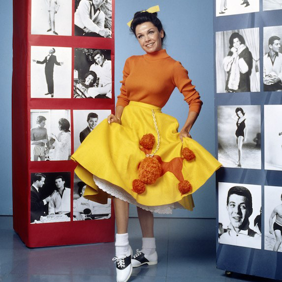 Actress Annette Funicello is photographed on set wearing a yellow poodle skirt, orange turtleneck and saddle shoes