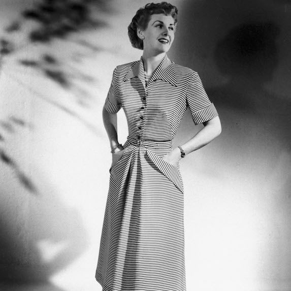 Woman in a black and white photo from the 1940's poses in a dress