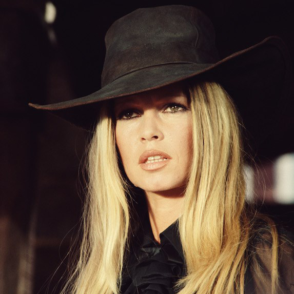 Brigitte Bardot wears a wide brimmed hat while working on the set of film in the 1970's