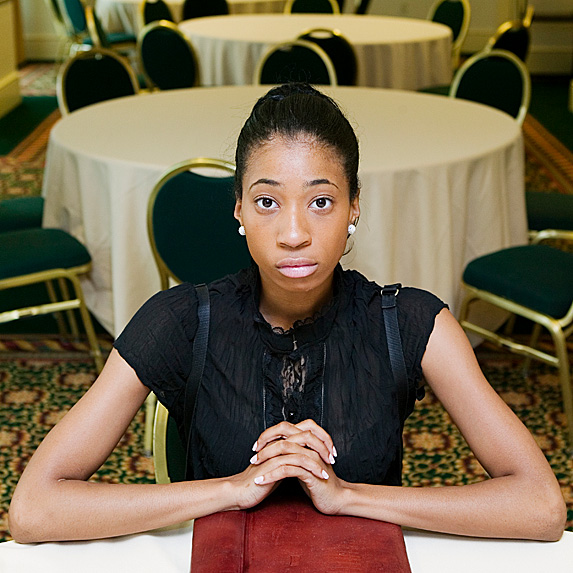 Nervous-looking young woman sitting at table in banquet hall