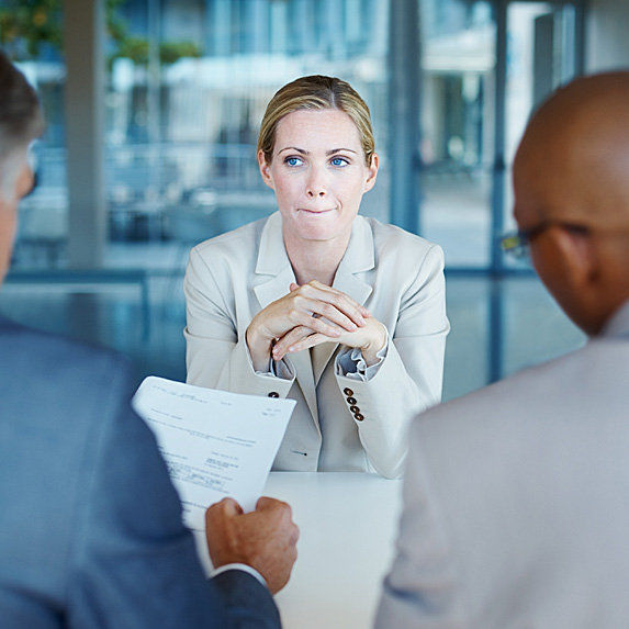 Nervous-looking woman facing two interviewers