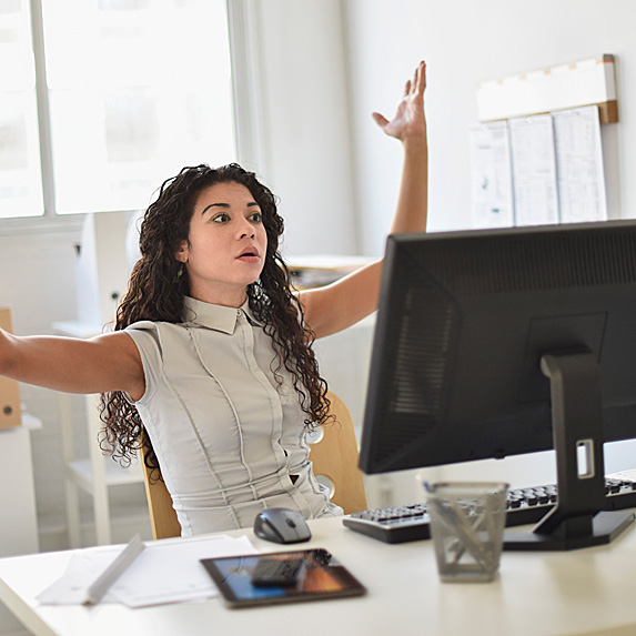 Woman holding arms up in disgust at desk