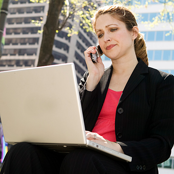 Woman outside on phone while looking at laptop