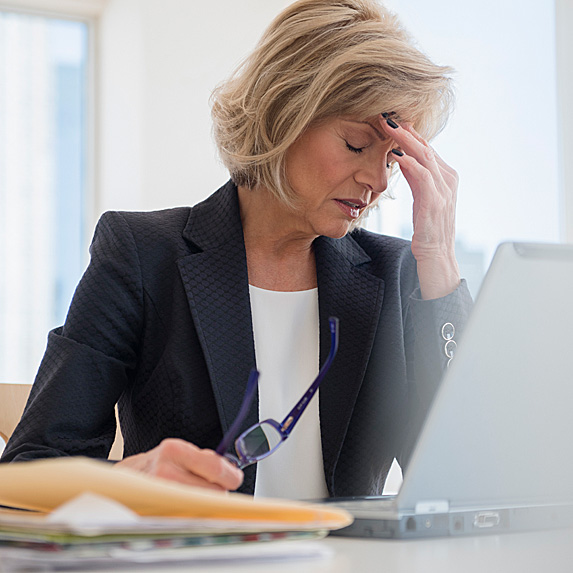 Woman rubbing forehead at desk