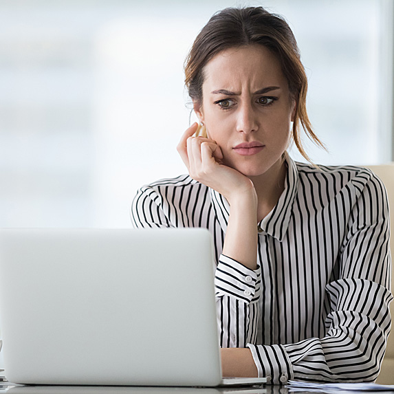 Confused woman looking at laptop
